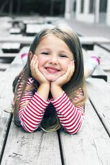 Bambina distesa su una panca in legno