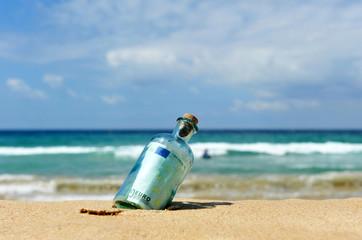 Botella con dinero en la playa
