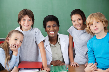 Cute Schoolchildren With Female Teacher At Desk