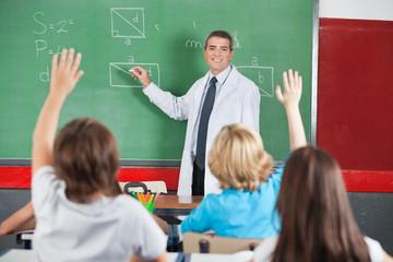 Teacher Teaching While Students Raising Hands