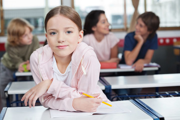 Schoolgirl Leaning On Desk With Students In Background