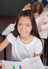 Schoolgirl Sitting At Desk In Classroom