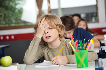 Tired Schoolboy Sitting At Desk In Classroom