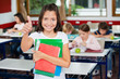 Schoolgirl Gesturing Thumbs Up While Holding Books