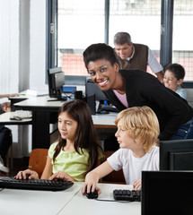 Female Teacher With Students At Desk