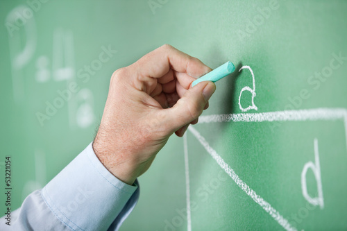 Mature Teacher'S Hand Writing Alphabet On Greenboard