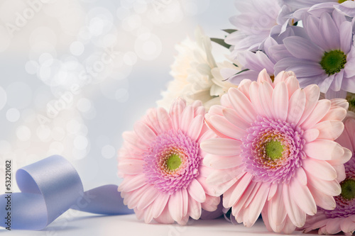 Pink gerbera daisies with blue ribbon.