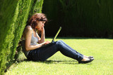 Attractive woman sitting on the grass bored with a laptop