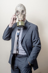 businessman with gas mask with phone
