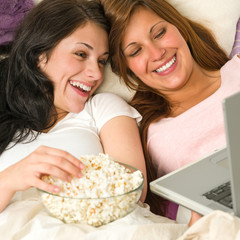Sisters lying on bed watching funny movie