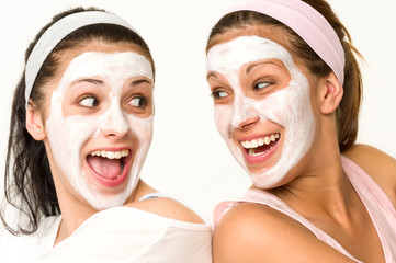 Cheerful girls having facial mask and laughing
