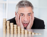 Shocked Businessman With Stack Of Coins