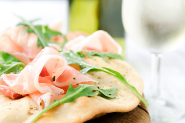 Gourmet pizza with proscuitto and wine