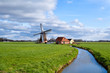charming dutch windmill on green grasslands