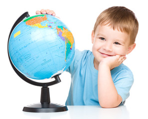 Happy little boy with a globe