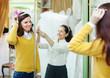saleswoman helps bride chooses bridal accessories