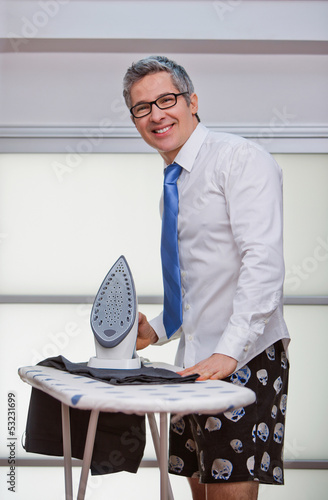 Portrait of a businessman smiling while ironing pants