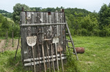 Used farm hand implements on wooden shed wall background poster