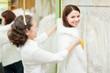 consultant helps bride chooses fur cape
