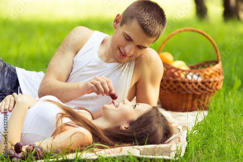 man feeding woman grapes