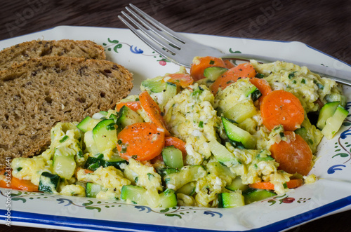 Scrambled eggs with vegetables and bread