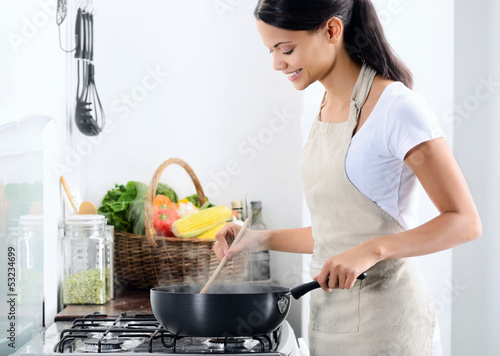 Pretty asian woman wearing an apron cooking in the kitchen