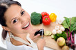 Smiling woman in the kitchen chopping vegetables