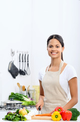 Smiling woman slicing vegetables in a kitchen