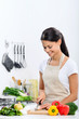 Smiling woman in the kitchen preparing healthy meal