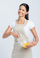 Portrait of happy indian woman whisking eggs for baking