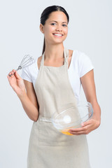 Confident homemaker chef with whisk and glass bowl of eggs