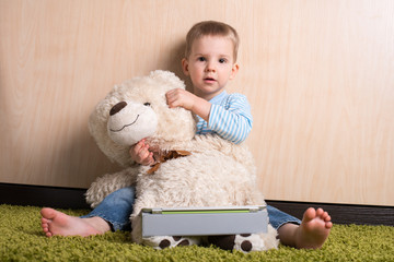 Boy and teddy bear with tablet computer