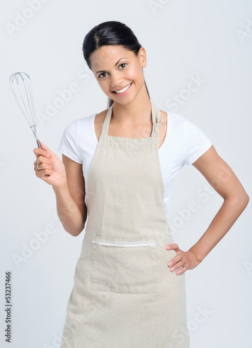 Beautiful mix race woman holding kitchen whisk