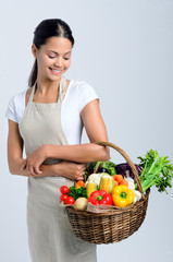 Woman with raw fresh produce ingredients in a basket