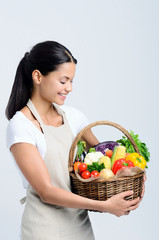 Attractive woman holding a basket of vegetables