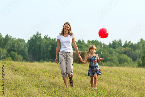 Mother and daughter go forward with ball in hand