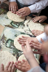 children arms making doughs at pizza workshop