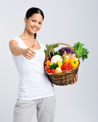Happy woman holding basket of raw vegetables