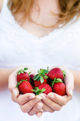 Woman holding strawberries in her hand
