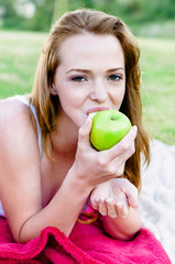 Healthy woman eats apple outdoors