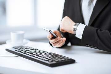 man hands with keyboard, smartphone and wristwatch