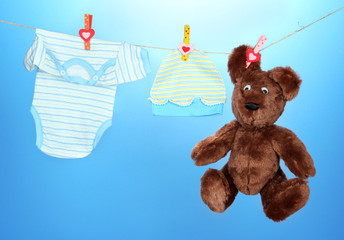 Baby clothes hanging on clothesline, on blue background
