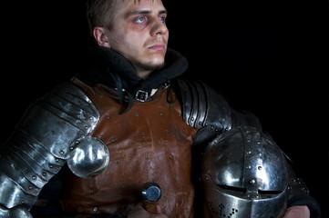 Warrior holding helmet on a black background