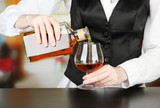 Barman hand with bottle of cognac  pouring drink into glass,