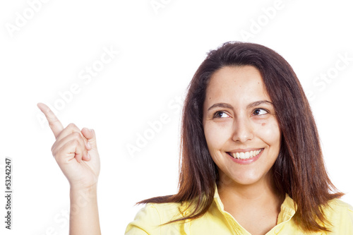 Smiling young casual woman pointing her finger to copy space