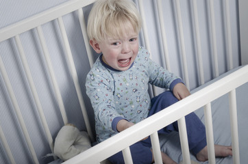 little boy crying in bed