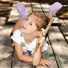 Bambina distesa a pancia in giù con un mazzetto di fiori
