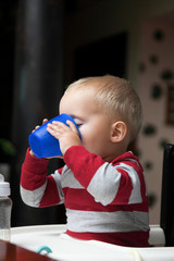 baby boy playing with bottle and mug indoor