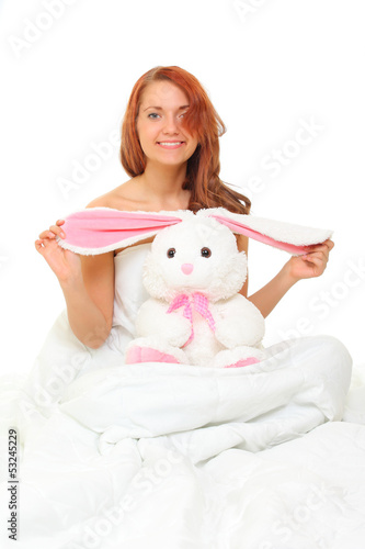 young woman in bed with a plush hare