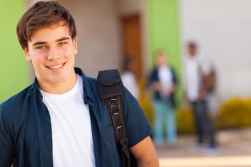 teen boy carrying schoolbag